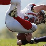 Photo: Man tripped over by other player - in mid-air holding an American football.