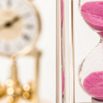 Photo: Hourglass with pink sand. Gold clock in background.