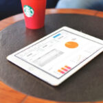 Photo: Tablet and coffee on round table.
