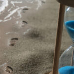 Photo: Hourglass on the beach with footsteps along water.